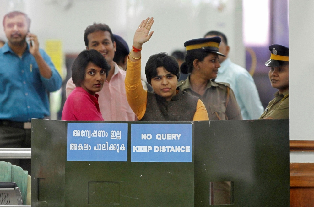 Trupti Desai, a women's rights activist, waves from inside the Cochin International Airport at Kochi, India, on Friday. — Reuters