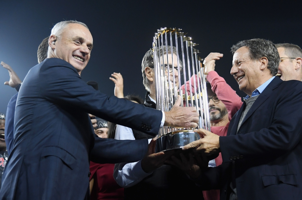 In this file photo, MLB Commissioner Rob Manfred presents the World Series trophy to John W. Henry and Tom Werner after the teams 5-1 win over the Los Angeles Dodgers in Game Five of the 2018 World Series at Dodger Stadium in Los Angeles, California. Major League Baseball owners unanimously voted on Wednesday to extend commissioner Rob Manfred's contract for five years through the 2024 season, the same day the league announced a television contract extension. — AFP