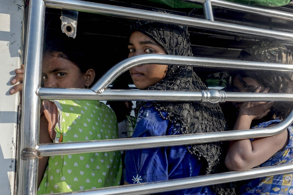 Rohingya Muslim women ride a police vehicle in Kyauktan township south of Yangon on Friday after their boat washed ashore. — AFP