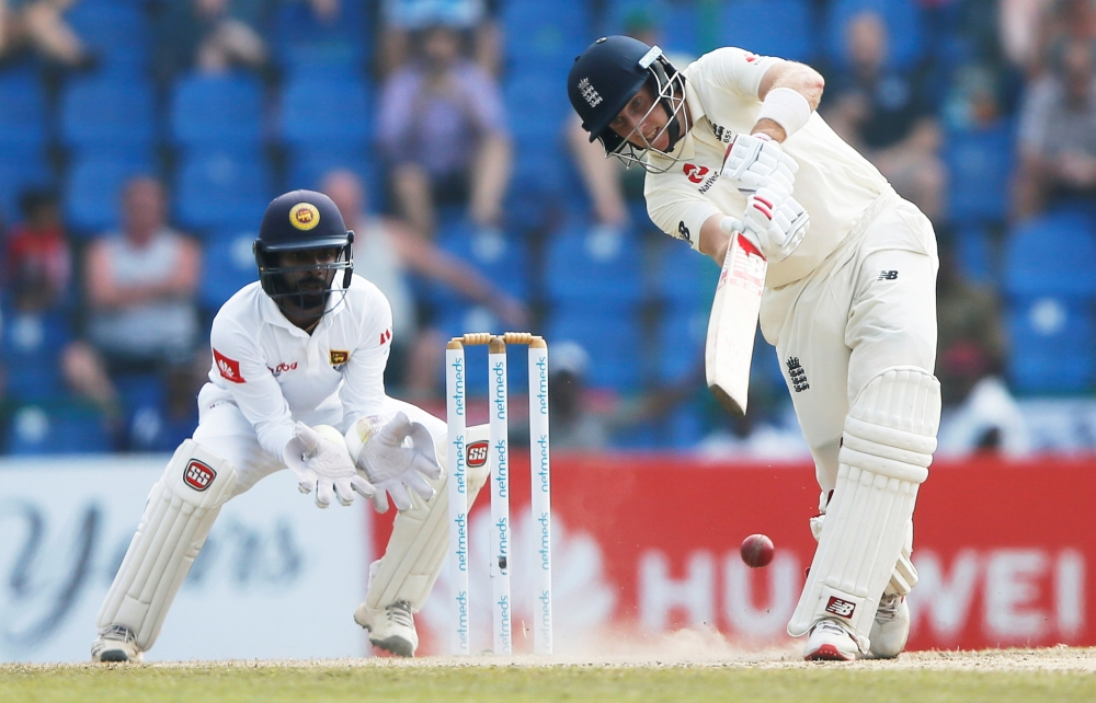 England's captain Joe Root (R) plays a shot next to Sri Lanka's wicketkeeper Niroshan Dickwella during the second cricket Test at Pallekele, Sri Lanka, on Friday. — Reuters