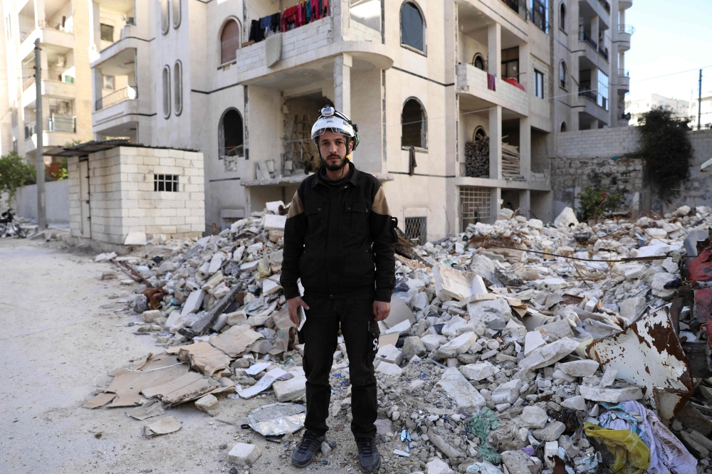 Mohammed Hamroush, a 29-year-old member of the Syrian civil defense holds his smartphone as he poses for a picture in front of damaged buildings, in the town of Zardana in the rebel-held northern countryside of Idlib, in this October 29, 2018 file photo. — AFP