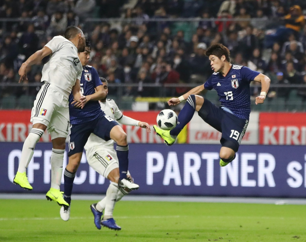 Japan's defender Hiroki Sakai (R) shoots to score a goal during the friendly football match between Japan and Venezuela in Oita on Friday. — AFP