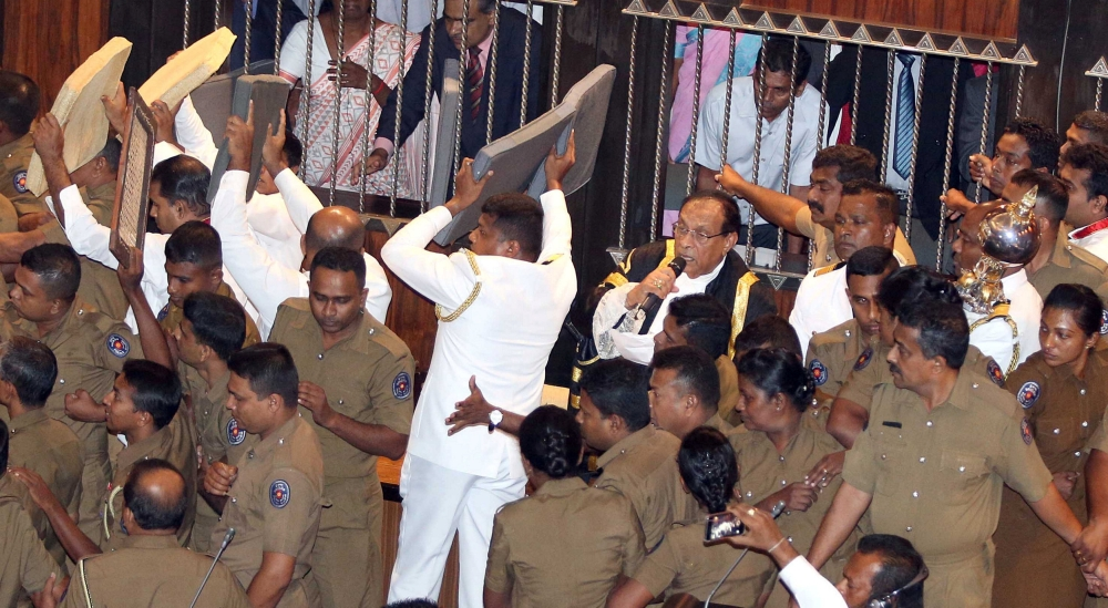 Sri Lankan police members protect parliament speaker Karu Jayasuriya, in a black jacket, center, as he tries to walk to his chair while parliament members who are backing newly appointed Prime Minister Mahinda Rajapaksa protest during the parliament session in Colombo on Friday. — Reuters