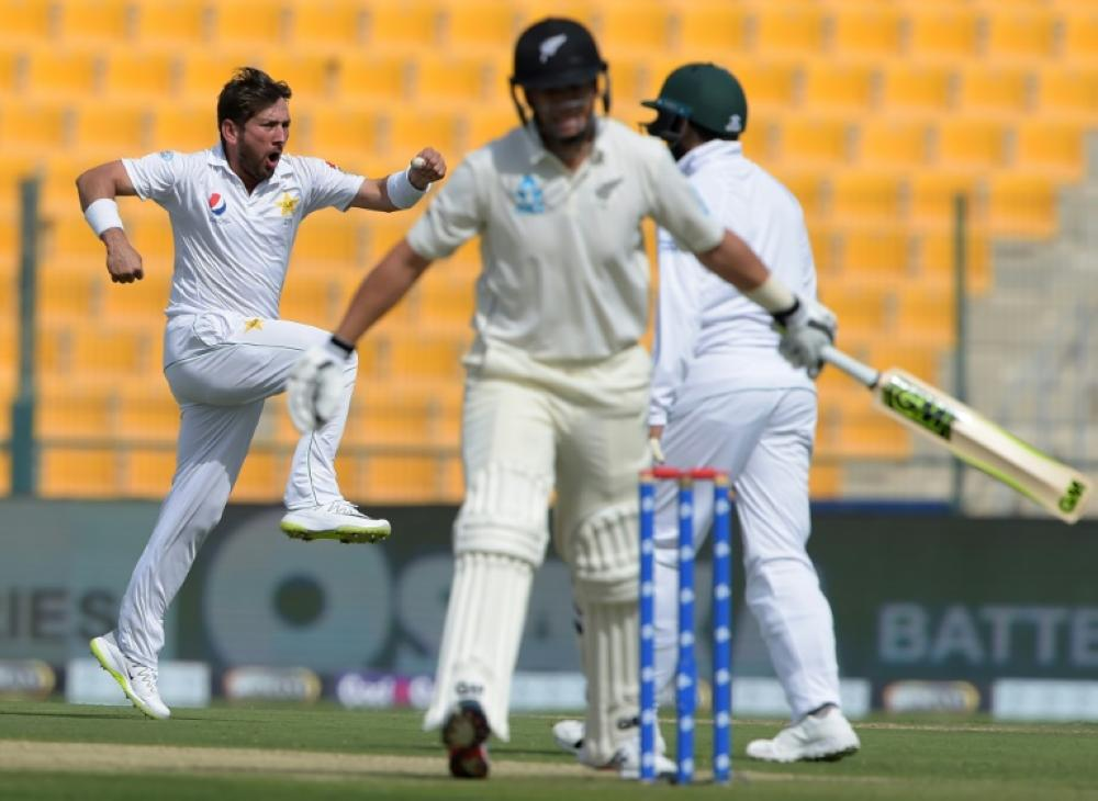 Pakistan spinner Yasir Shah (L) celebrates after taking the wicket of New Zealand batsman Ross Taylor (C) on Friday. — AFP