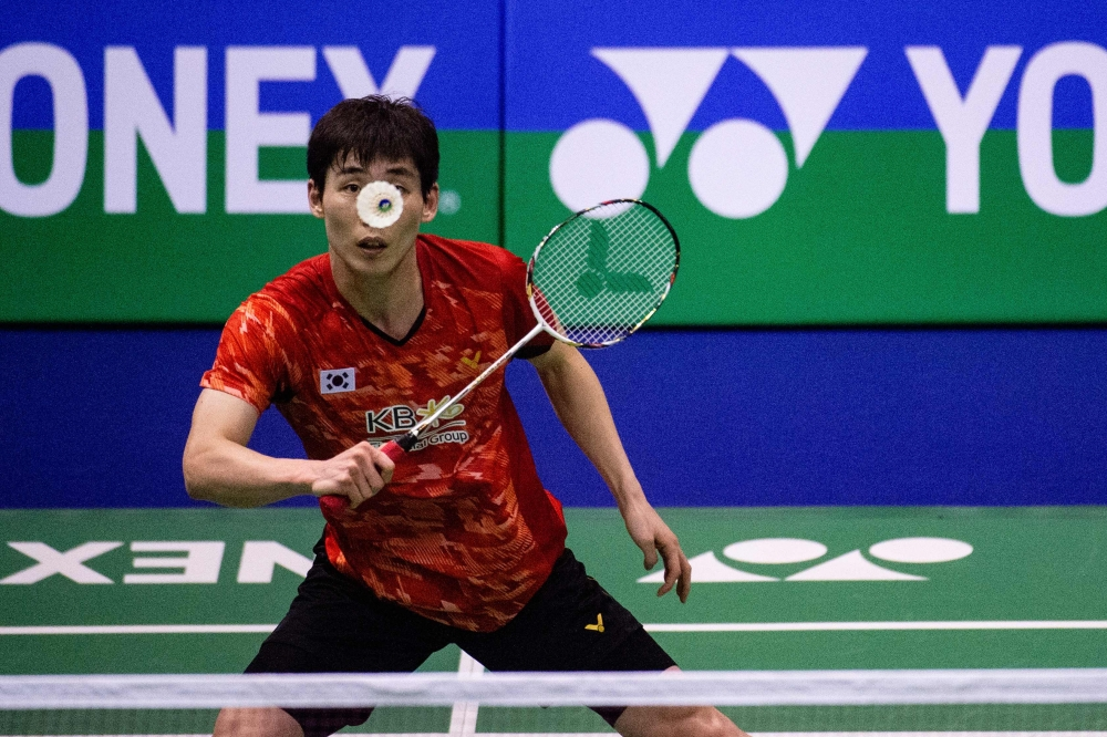 South Korea's Son Wan-ho hits a return against Kento Momota of Japan in their men's singles semifinal match at the Hong Kong Open badminton tournament on Saturday. — AFP