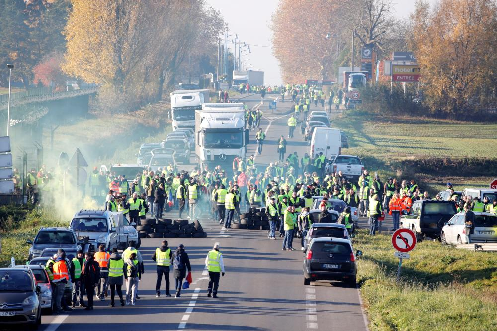 People wearing yellow vests, a symbol of a French drivers' nationwide protest against higher fuel prices, block the Paris-Brussels motorway in Haulchin, France, Saturday. — Reuters