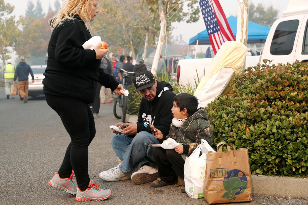 After losing their home in Magalia in the Camp Fire, Robin Tompkins and Timothy Payne eat a free meal with their son, Lukas, at a makeshift evacuation center in Chico, California, on Friday. — Reuters