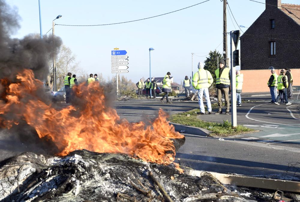 Demonstrators of the Yellow Vests movement (Gilets Jaunes) stand by a fire on Sunday on a roundabout in Douchy-les-Mines, near Valenciennes, northern France, a day after a nationwide protest against high fuel prices. — AFP