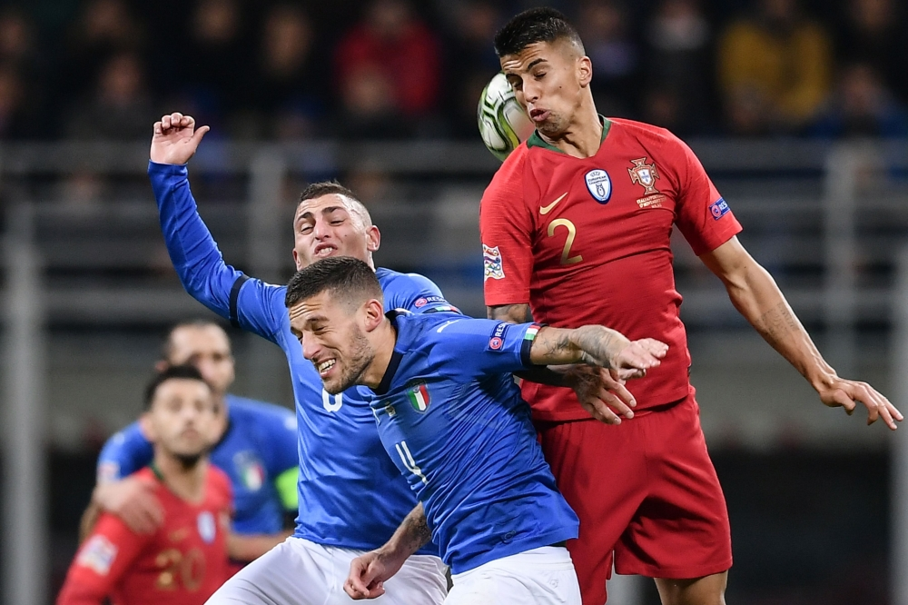 (From L) Italy's midfielder Marco Verratti, Italy's defender Cristiano Biraghi and Portugal's defender Joao Cancelo go for a header during the UEFA Nations League Group 3 football match at the San Siro Stadium in Milan on Saturday. — AFP