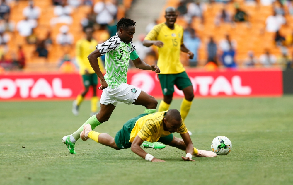 South Africa's Tiyani Mabunda is tackled by Nigeria's captain Ahmed Musa during the African Cup of Nations qualifier match between South Africa and Nigeria on Saturday at Soccer City Stadium in Johannesburg, South Africa. — AFP