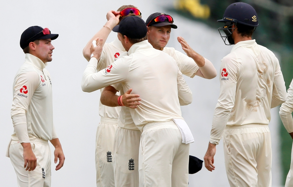 England's captain Joe Root (2nd R) congratulates his teammates after they won the second cricket Test match against Sri Lanka at Pallekele, Sri Lanka, on Sunday. — Reuters