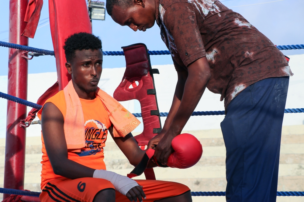 Somali boxer Abdiaziz Ali Shirar, 21-years-old, is helped with his glove by his coach during a boxing match in a ring installed at the Wish Stadium in Mogadishu.  Somalia has held its first boxing competition in over three decades, with young boxers in the conflict-torn nation dreaming of a career on the international stage. The three-day light-weight boxing competition, which wrapped up on Sunday. — AFP