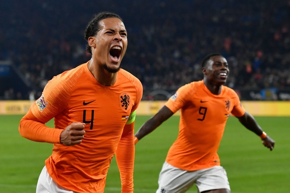 Netherlands' defender Virgil van Dijk (L) celebrates scoring the 2-2 with Dutch forward Quincy Promes during the UEFA Nations League football match against Germany in Gelsenkirchen on Monday. — AFP