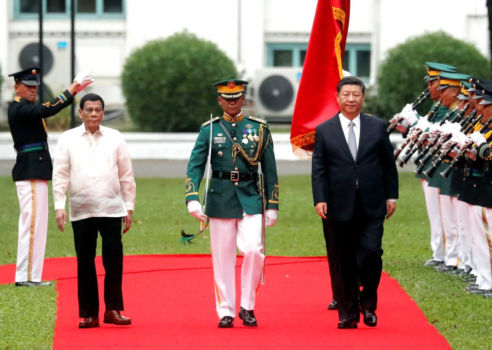 Visiting Chinese President Xi Jinping, right, and Philippine President Rodrigo Duterte review troops during a welcoming ceremony for the Chinese leader at the Malacanang presidential palace in Manila on Tuesday. — Reuters