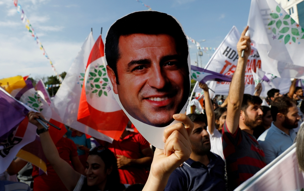 A supporter of the pro-Kurdish Peoples' Democratic Party (HDP) holds a mask of their jailed former leader and presidential candidate Selahattin Demirtas during a rally in Ankara, Turkey, in this June 19, 2018, file photo. — Reuters