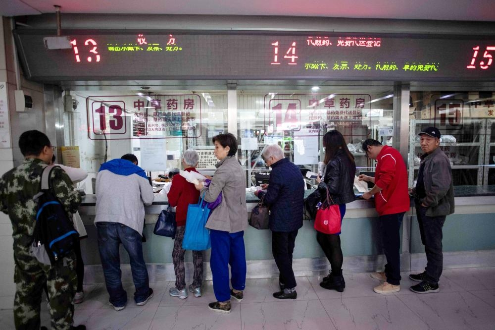 People queue up for medicine in the pharmacy of the Yueyang Hospital, part of the Shanghai University of Traditional Chinese Medicine, in Shanghai, in this Nov. 7, 2018 file photo. — AFP