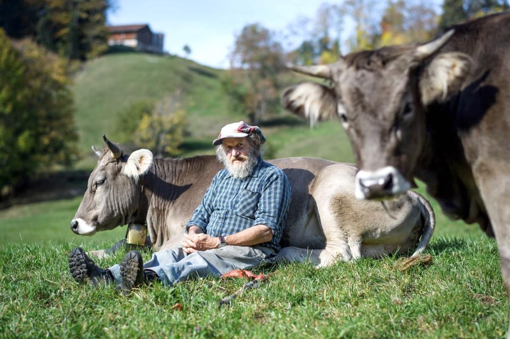 Swiss farmer Armin Capaul poses with one of his cows ahead of the nationwide vote on his initiative on cow horns, near Perrefitte, northern Switzerland, in this Oct. 16, 2018 file photo. — AFP    Capaul launched and collected more that 100,000 signatures for an initiative to offer monetary assistance to owners who don't dehorn their livestock. Swiss citizen will vote on the issue on November 25, 2018.  -   / AFP / Fabrice COFFRINI