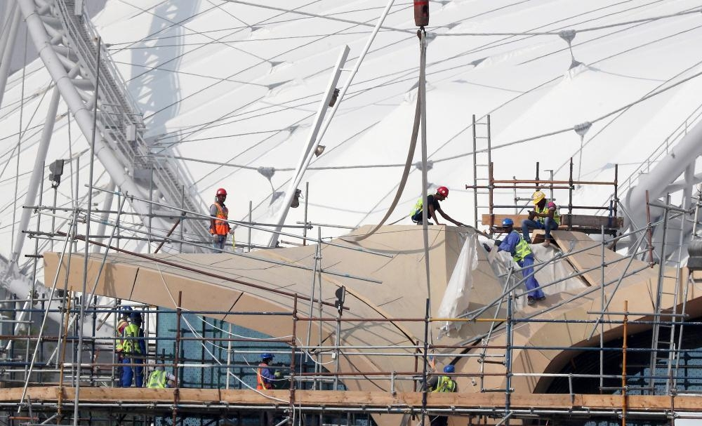 Workers are pictured on scaffolding at the Khalifa International Stadium in Doha. —  AFP