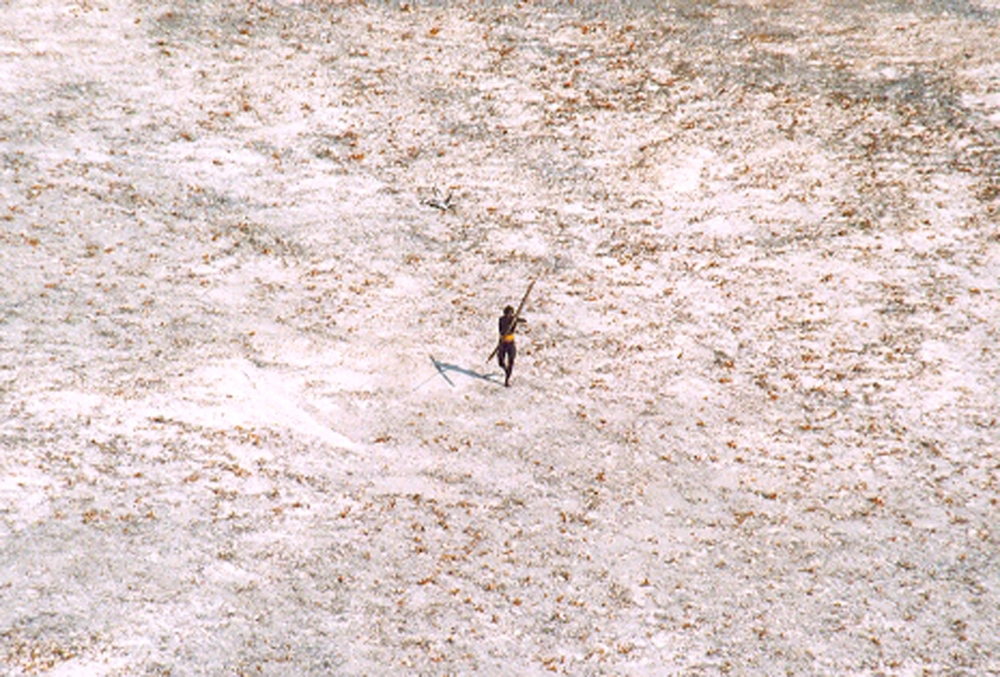 A Sentinel tribal man aims with his bow and arrow at an Indian Coast Guard helicopter as it flies over the island for a survey of the damage caused by the tsunami in India's Andaman and Nicobar archipelago in this Dec. 28, 2004 file photo. — Reuters