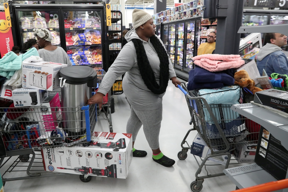 People wait in line to pay at a Walmart during a sales event on Thanksgiving day in Westbury New York US on Thursday. — Reuters