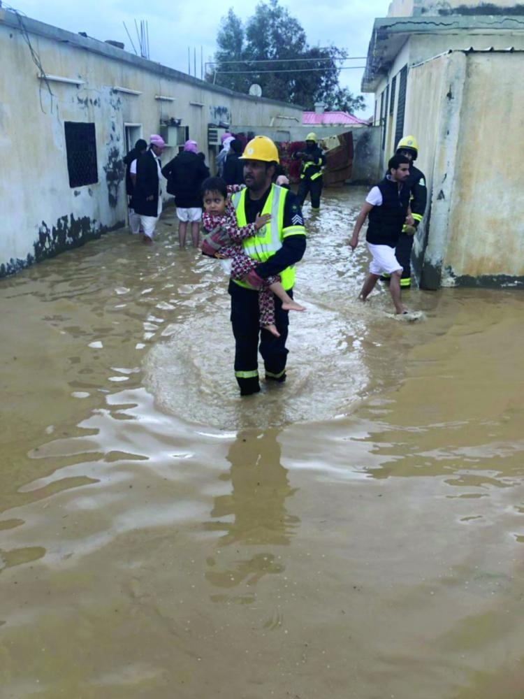 Rescue teams evacuate people trapped by floodwaters in Al-Jouf.