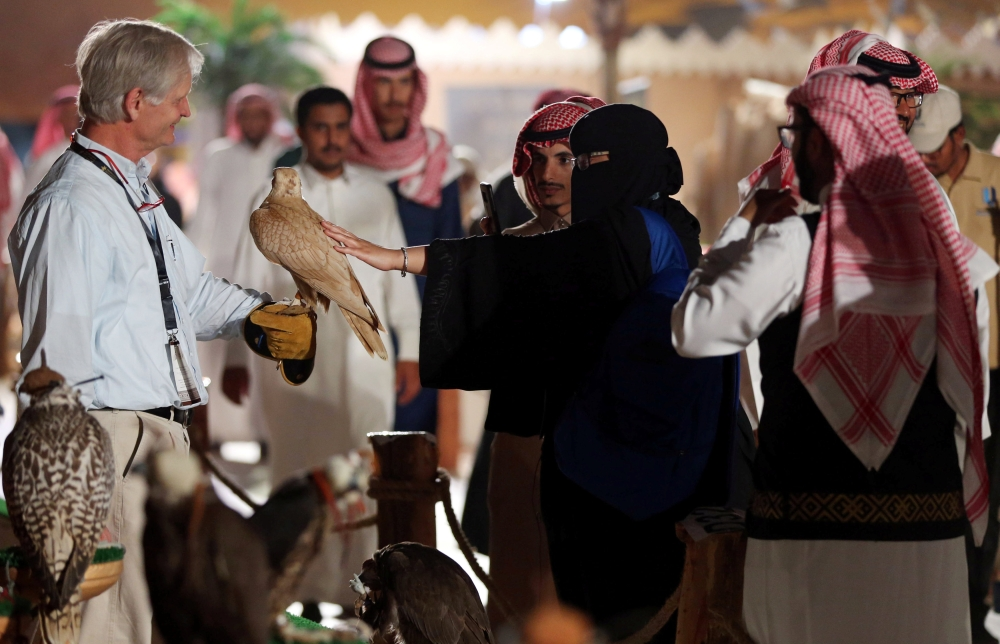A woman touches a falcon at the first Saudi Falcons and Hunting Exhibition in Riyadh, Saudi Arabia, December 5, 2018. REUTERS