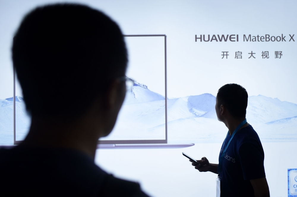 This file photo shows men looking at an LED display board of Huawei at the Beijing International Consumer Electronics Expo in Beijing. China reacted furiously on Thursday after a top executive and daughter of the founder of Chinese telecom giant Huawei was arrested in Canada following a US extradition request, threatening to rattle a trade war truce with the United States.  — AFP