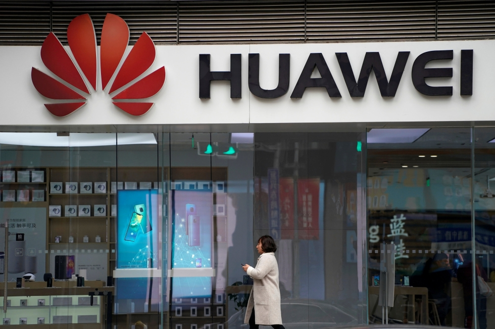 A woman walks by a Huawei logo at a shopping mall in Shanghai, China, in this recent photo. — Reuters