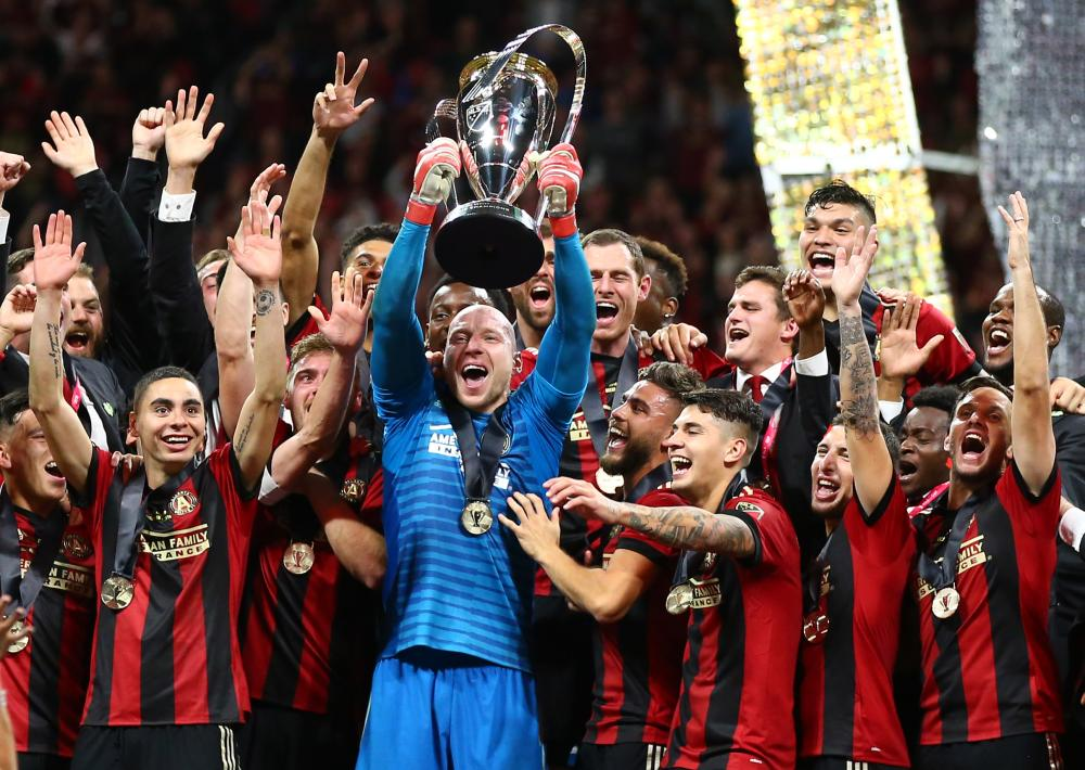Atlanta United's goalkeeper Brad Guzan and teammates hoist the trophy after defeating the Portland Timbers in the 2018 MLS Cup championship game at Mercedes-Benz Stadium in Atlanta Saturday. — Reuters