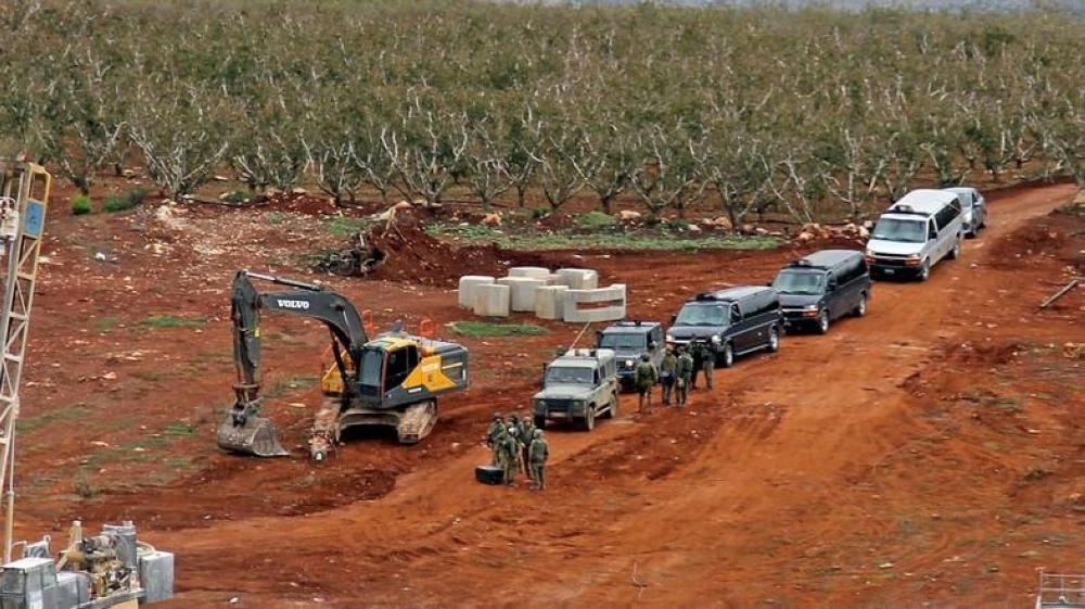 A picture taken on Dec. 5, 2018 near the southern Lebanese village of Kfar Kila shows members of the Israeli military, excavators and trailers operating on the other side of the border. — AFP