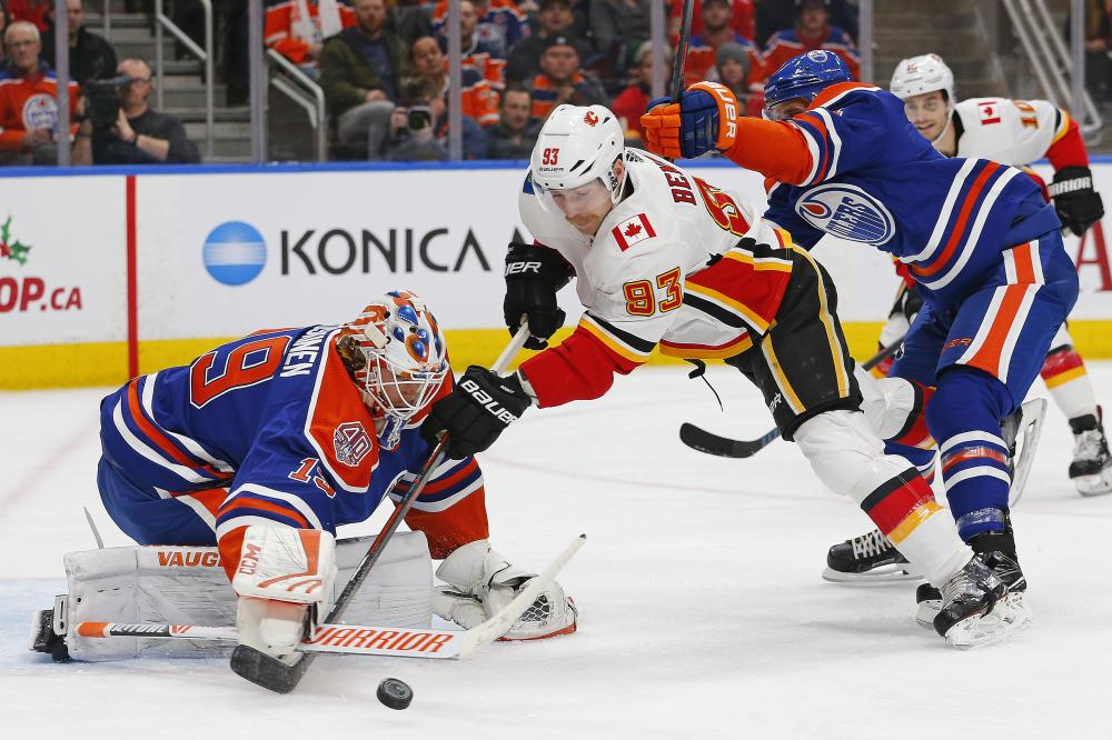Edmonton Oilers' goaltender Mikko Koskinen makes a save on Calgary Flames' forward Sam Bennett during their NHL game at Rogers Place in Edmonton Sunday. — Reuters
