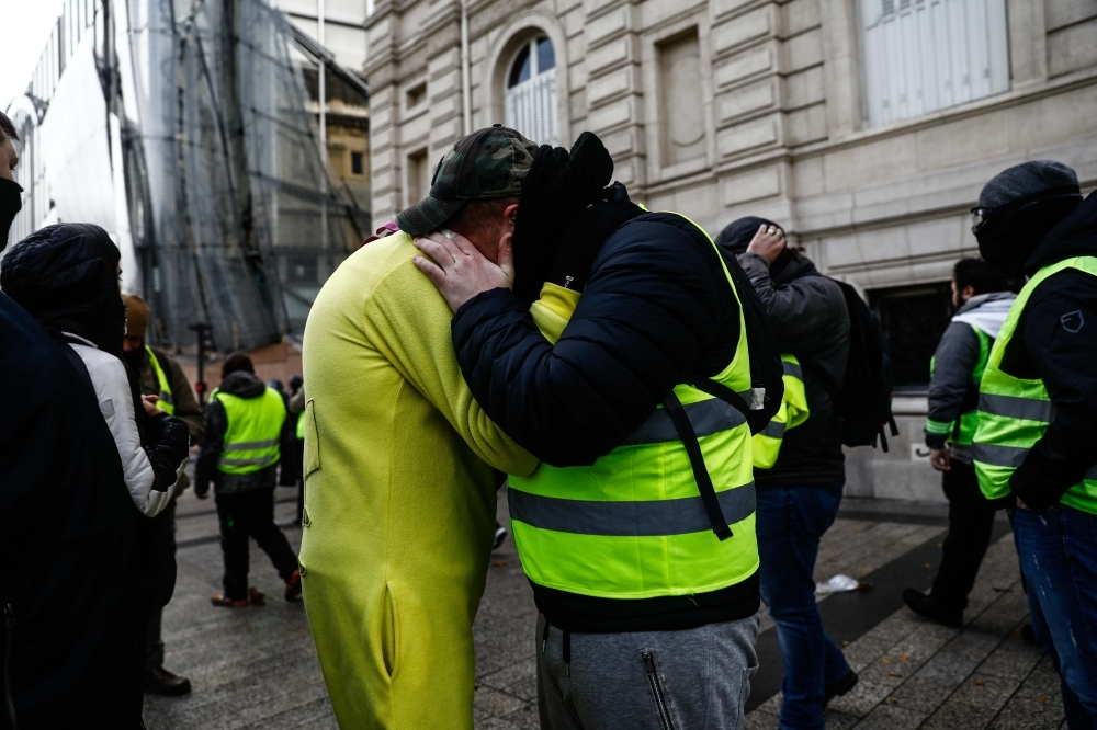 Protesters wearing yellow vests (Gilets jaunes) hug on the Champs Elysees in Paris on Saturday during a protest against rising costs of living they blame on high taxes. — AFP