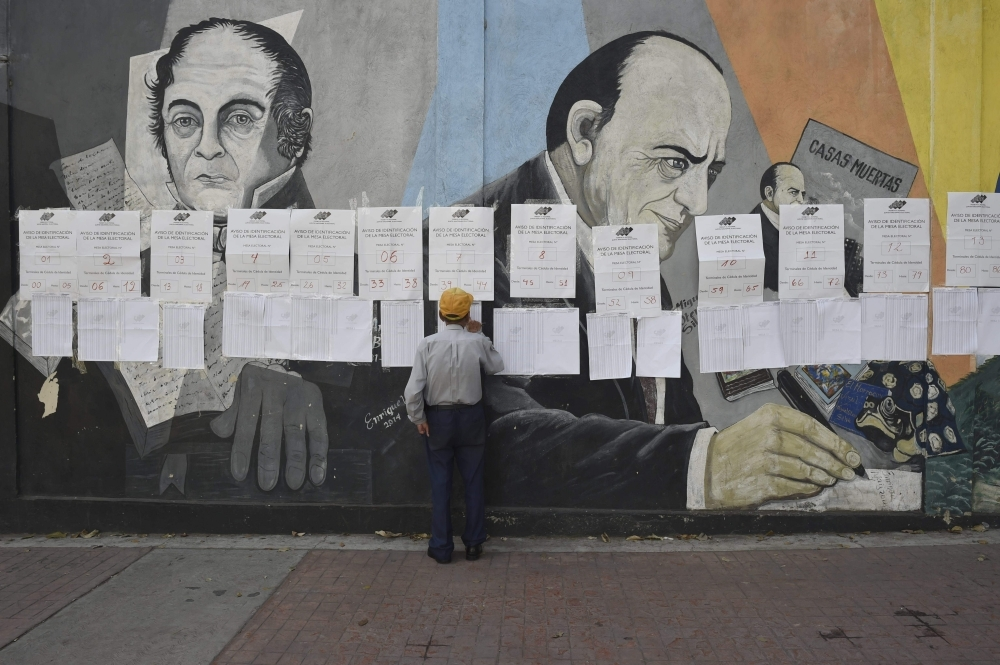 A voter looks for his name at a polling station in Caracas during Venezuelan municipal council elections on Sunday. — AFP