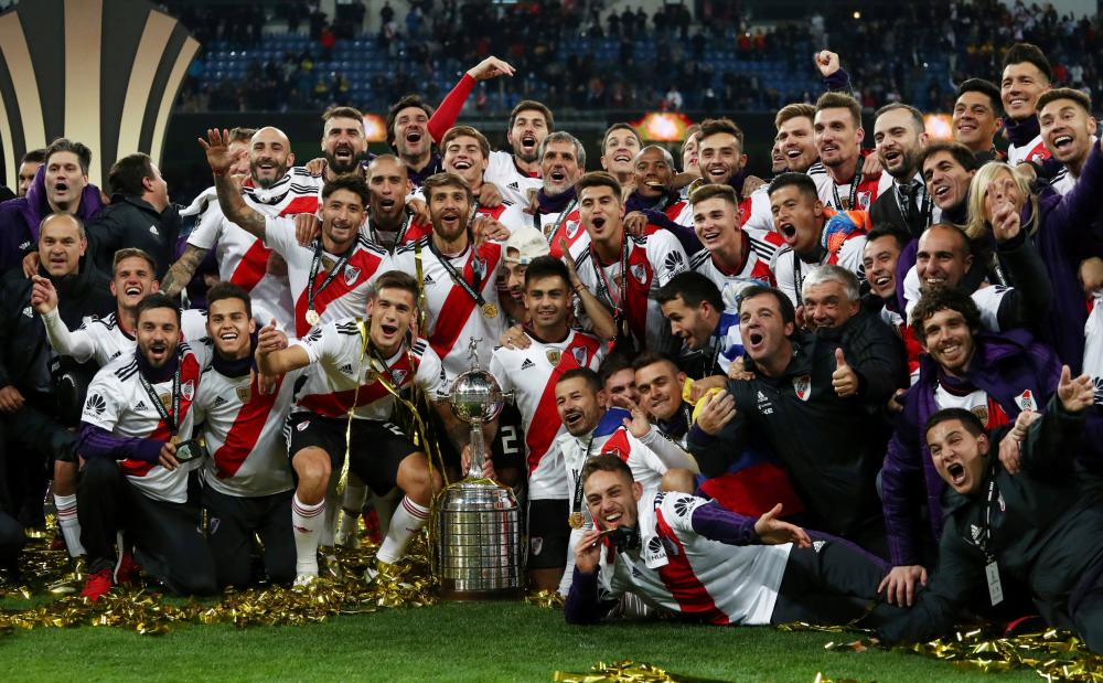 River Plate players celebrate with the trophy after winning the Copa Libertadores final against Boca Juniors at Santiago Bernabeu Stadium in Madrid Sunday. — Reuters