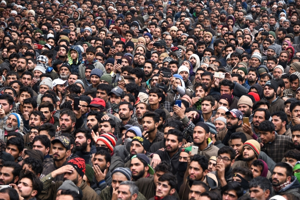 Kashmiri villagers look on during the funeral procession of slain teenager militant Mudasir Ahmad Parrey, 14, in Hajin, north of Srinagar, on Monday. — AFP