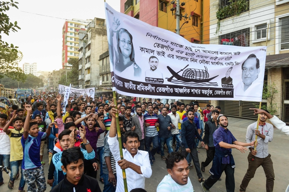 Supporters of Bangladesh Awami League march in the street as they take part in a general election campaign procession in Dhaka on Monday. — AFP