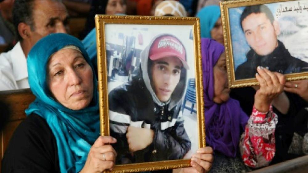 Families of victims of Tunisia's 2011 revolt against dictatorship carry portraits of their loved ones during a trial in Kasserine in this July photo. — AFP