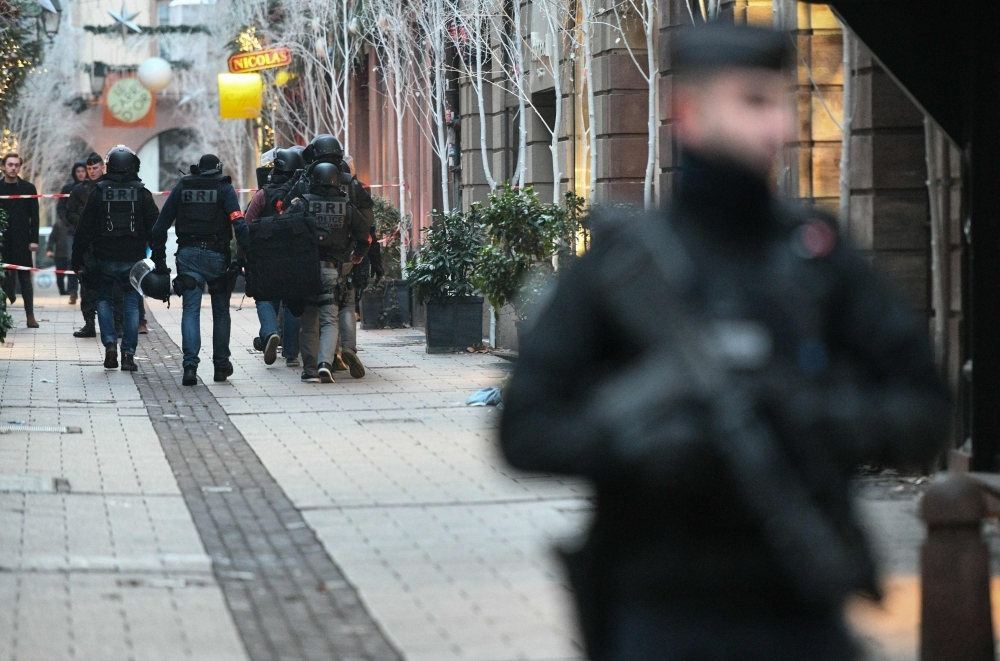 Members of the French police unit BRI (Research and Intervention Brigade —  Brigades de recherche et d'intervention) conduct searches in the rue des orfevres on Wednesday for the gunman who opened fire near a Christmas market in Strasbourg, eastern France, on Tuesday night. — AFP