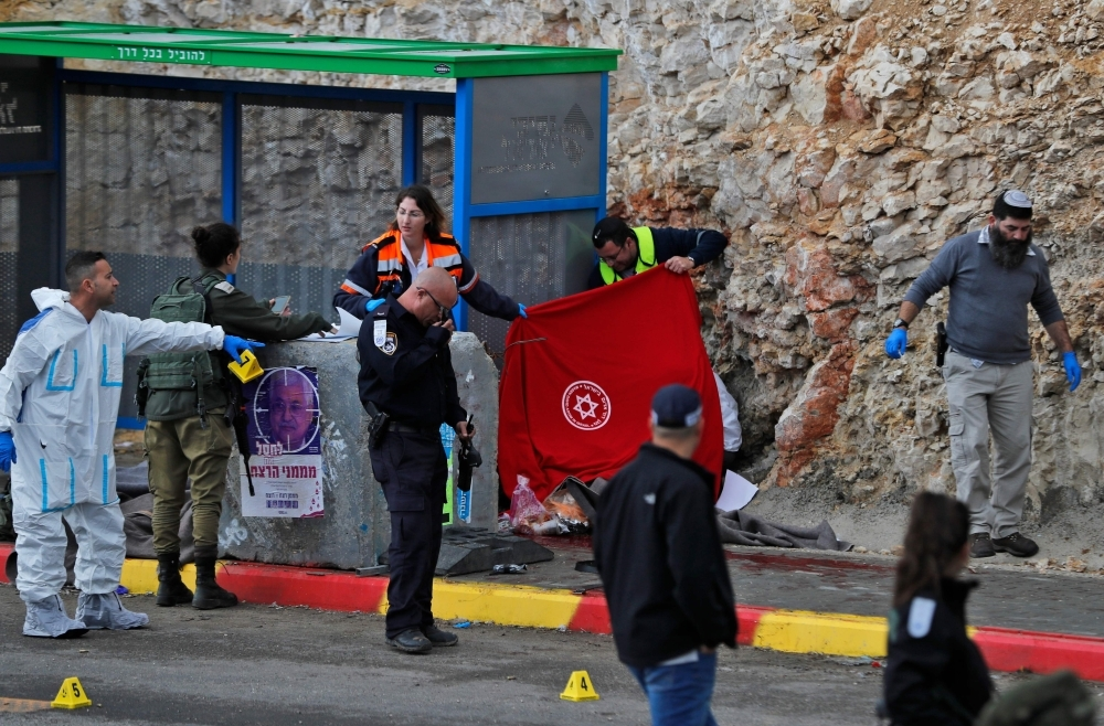 Israeli forces and forensic experts inspect the site of a Palestinian drive-by shooting attack outside the West Bank settlement of Givat Asaf, northeast of Ramallah, on Thursday. — AFP