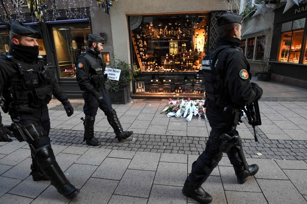 French gendarmes walk past flowers and candles laid in the street in tribute to the victims of a deadly shooting two days ago in central Strasbourg, France, on Thursday. — AFP