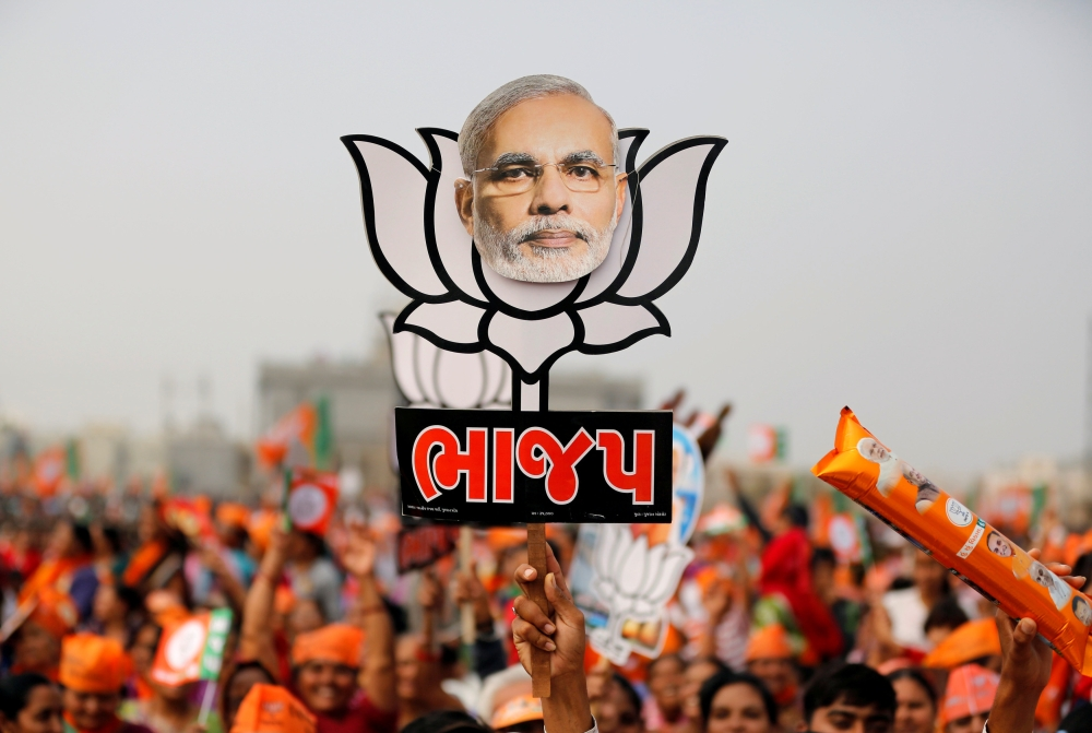 A supporter holds up a cut-out of a lotus, the election symbol of India's ruling Bharatiya Janata party (BJP), with an image of Prime Minister Narendra Modi during a campaign meeting addressed by Modi ahead of Gujarat state assembly election in Kalol on the outskirts of Ahmedabad, India, in this Dec. 8, 2017 file photo. — Reuters