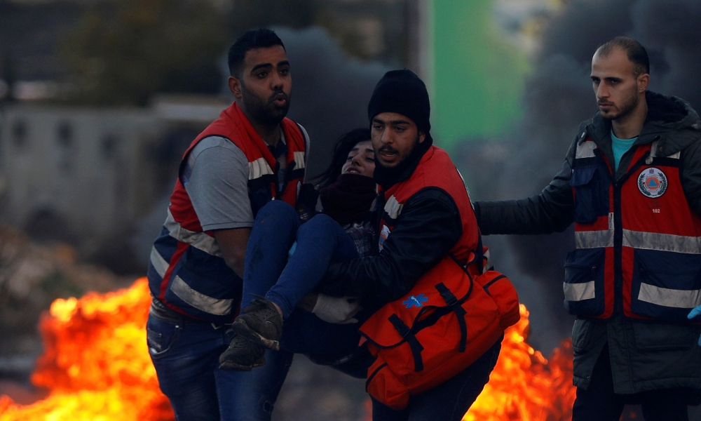 Medics evacuate a wounded Palestinian woman during clashes with Israeli troops near the Jewish settlement of Beit El, near Ramallah, in the Israeli-occupied West Bank, on Thursday. — Reuters