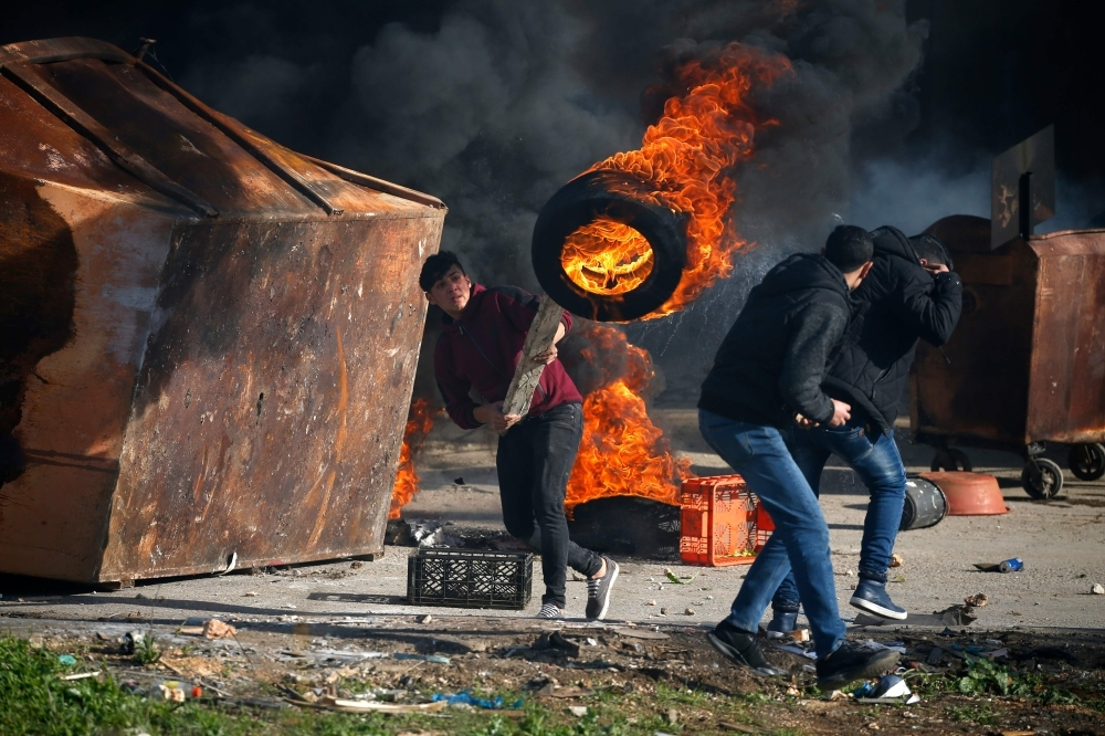 A Palestinian uses a piece of wood to move a burning tire during clashes with Israeli troops in Ramallah, near the Jewish settlement of Beit El, in the occupied West Bank on Thursday. — AFP