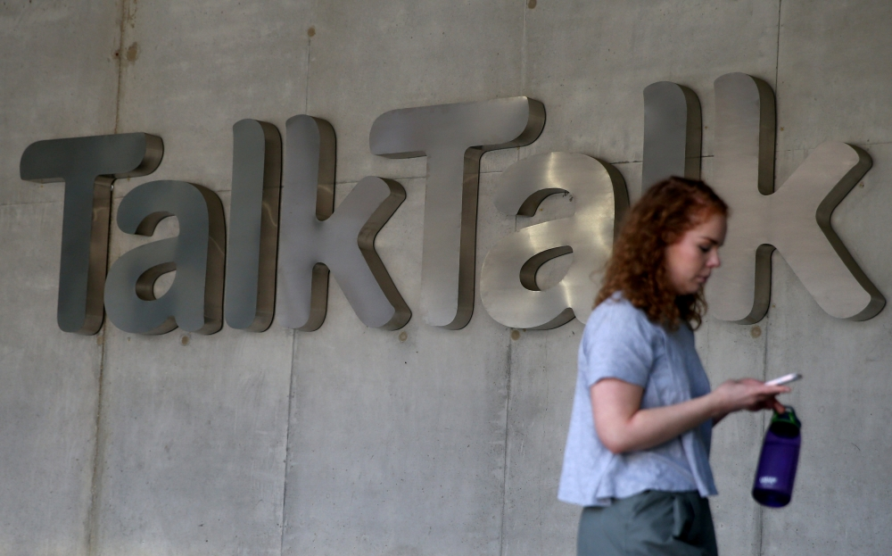 A woman views her phone as she passes a branded logo outside the Talktalk headquarters in London, Britain, in this file photo. — Reuters