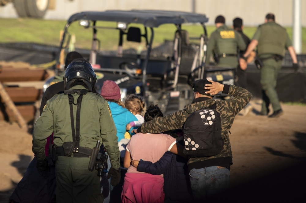Central American migrants, traveling in a caravan, are taken into custody by US border patrol officers after crossing the Mexico-US border fence to San Diego County, as seen from Playas de Tijuana, Baja California state, Mexico, on Thursday. — AFP