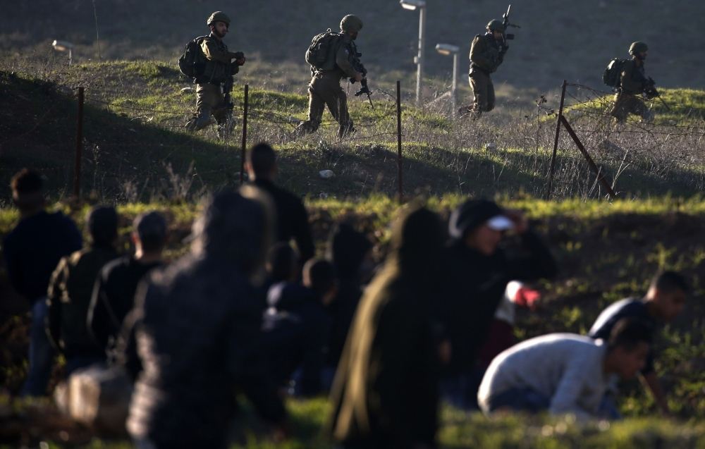 Israeli soldiers take position on a hillside facing Palestinian protesters during demonstrations near the Hawara checkpoint south of the occupied West Bank city of Nablus on Friday. — AFP