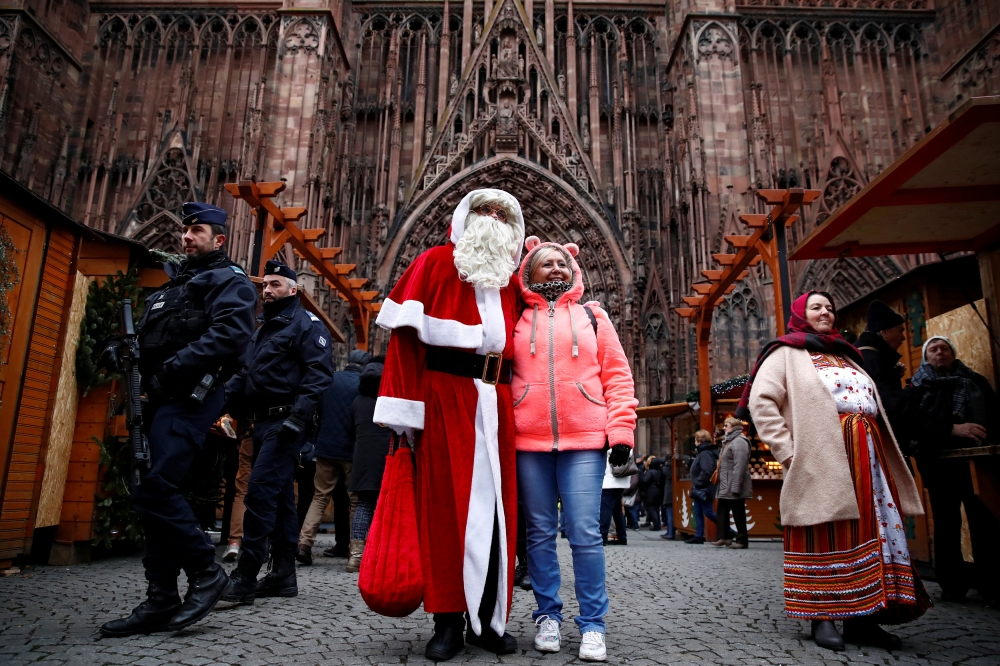 French police patrol outside the Strasbourg Cathedral as a man dressed as Father Christmas poses with a tourist, in Strasbourg, France, on Friday. — Reuters