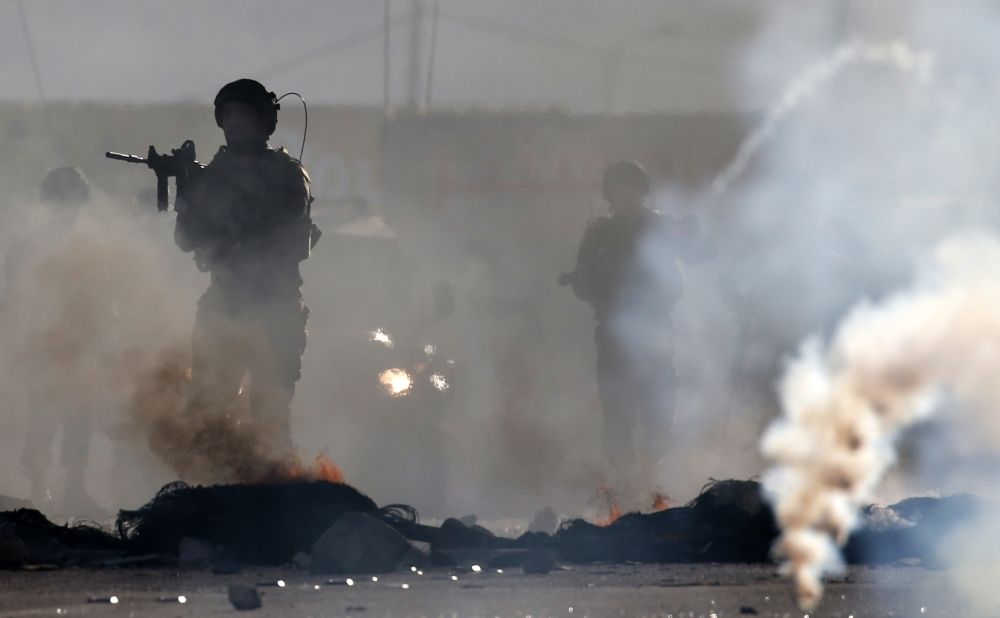 Israeli soldiers react amid burning tires and tear gas near the Hawara checkpoint, during clashes with Palestinian demonstrators, south of the occupied West Bank city of Nablus, Friday night. — AFP