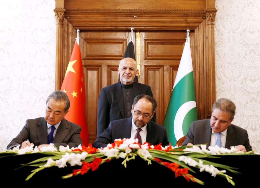 Afghanistan's Foreign Minister Salahuddin Rabbani (sitting-center), Pakistan's Foreign Minister Shah Mehmood Qureshi and Chinese Foreign Minister Wang Yi sign a memorandum of understanding on cooperation in fighting terrorism in Kabul, Afghanistan, Saturday. — Reuters