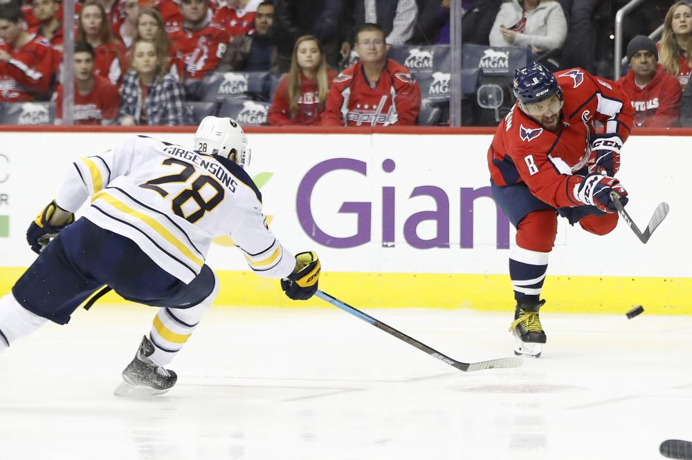 Washington Capitals' left wing Alex Ovechkin (R) shoots the puck as Buffalo Sabres' center Zemgus Girgensons defends during their NHL game at Capital One Arena Saturday. — Reuters